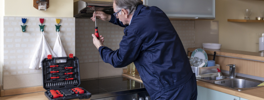 Senior Working Man is Fixing an Extractor Fan at Home.