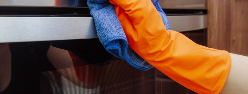 Hand with a microfiber cloth is being wiped on the outside of the electric oven.